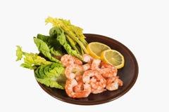 Peeled Prawns & lemon. Plate of peeled prawns with slices of lemon, lettuce and celery Stock Photography