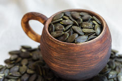 Peeled pumpkin seeds are in earthenware mug. Stock Photos