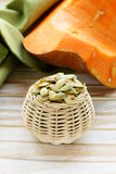 Peeled pumpkin seeds and fresh pumpkin Royalty Free Stock Images