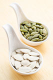 Peeled pumpkin seeds. Peeled pumpkin seeds in white spoon on wooden background royalty free stock image