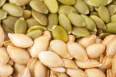 Peeled pumpkin seeds or whole background macro Royalty Free Stock Images