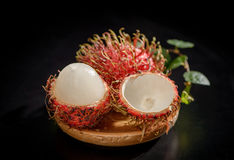 Peeled rambutan fruits with vanilla on wooden plate isolated   on black background Royalty Free Stock Photo