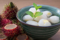 Peeled rambutan stuffed with pineapple in syrup. Peeled rambutan fresh stuffed with pineapple in syrup, in a green bowl ready to eat with wooden background Royalty Free Stock Photos