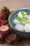 Peeled rambutan stuffed with pineapple in syrup. Peeled rambutan fresh stuffed with pineapple in syrup, in a green bowl ready to eat with wooden background Royalty Free Stock Images