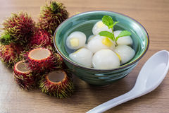 Peeled rambutan stuffed with pineapple in syrup. Peeled rambutan fresh stuffed with pineapple in syrup, in a green bowl with wooden background Stock Photo