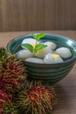 Peeled rambutan stuffed with pineapple in syrup. Peeled rambutan fresh stuffed with pineapple in syrup, in a green bowl with wooden background Stock Photos