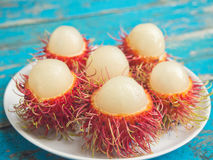 Peeled rambutans on white dish. Closeup of peeled rambutans served on white dish-Selective focus Stock Photos