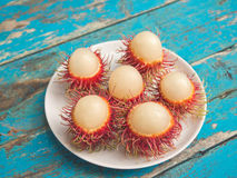 Peeled rambutans on white dish. View of peeled rambutans served on white dish with wooden table background Royalty Free Stock Photography