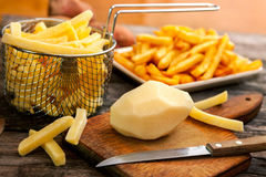 Peeled raw potato on chopping board with a knife. And potato in fry basket Stock Photos