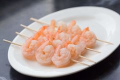 Peeled raw shrimp on sticks, cooking аsian skewers in kitchen Stock Images