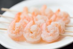 Peeled raw shrimp on sticks, cooking аsian skewers in kitchen Royalty Free Stock Photos