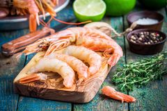 Peeled raw shrimps on a wooden cutting board with salt, pepper, lime Stock Images