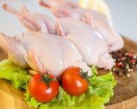 Peeled raw whole quail on wooden round board on white background. Stock Photo
