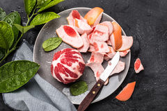 Peeled red grapefruit with knife on the grey plate Royalty Free Stock Images