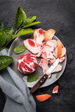 Peeled red grapefruit with knife on the grey plate Royalty Free Stock Photo