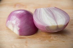 Peeled red onion, shallots on wood cutting Royalty Free Stock Images