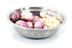 Peeled red shallots and garlic in stainless steel bowl Stock Images
