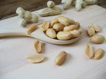 Peeled salted peanuts on wooden spoon Stock Images