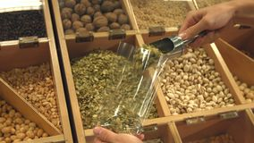 Peeled seeds and nuts. A man`s hand puts a pumpkin seed into a bag.