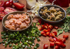 Peeled shrimp and mussels with chopped pepper and green onions tomatoes  a wooden background close up Royalty Free Stock Photos