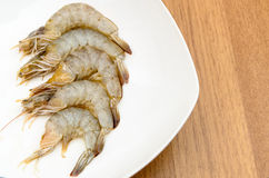 Peeled shrimps in white dish. Peeled shrimps prepare for cooking in white dish on wooden table Stock Images