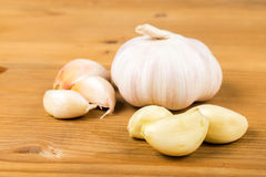 Peeled and sliced garlic cloves with whole garlic bulb and cloves as background Royalty Free Stock Photo