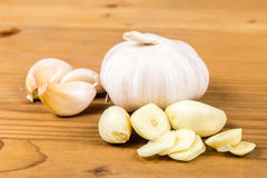 Peeled and sliced garlic cloves with whole garlic bulb and cloves as background.  Stock Photography