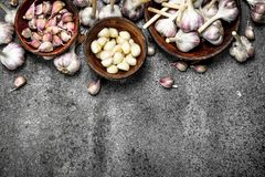 Peeled slices of fresh garlic in bowls. On a rustic background Stock Photo