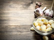 Peeled slices of garlic in a bowl. On a wooden table Royalty Free Stock Images