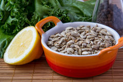 Peeled sunflower seeds. In orange cup with lemon Stock Photography