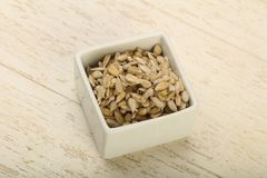 Peeled sunflower seeds. Heap over the wooden background Stock Photo
