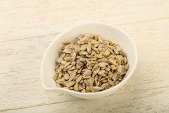 Peeled sunflower seeds. Heap over the wooden background Stock Image