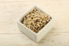 Peeled sunflower seeds. Heap over the wooden background Royalty Free Stock Photography