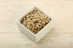 Peeled sunflower seeds. Heap over the wooden background Royalty Free Stock Images