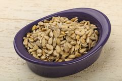 Peeled sunflower seeds. Heap over the wooden background royalty free stock photo