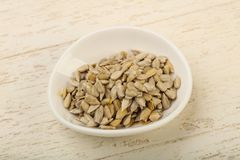 Peeled sunflower seeds. Heap over the wooden background Stock Photography