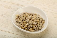 Peeled sunflower seeds. Heap over the wooden background Stock Images