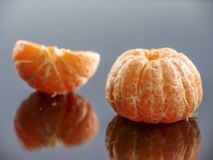 Peeled tangerine on a black mirror surface Stock Images
