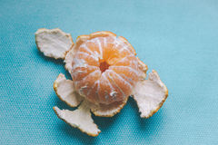 Peeled tangerine on blue background Stock Photography