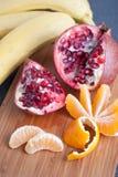 Peeled tangerine and cut pomegranate royalty free stock photo