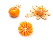 Peeled tangerine isolated on white. Two peeled tangerine and one unhulled isolated on white background Stock Images