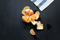 Peeled tangerine lies on the board. There are drops of juice and tangerine peel around. Royalty Free Stock Photo