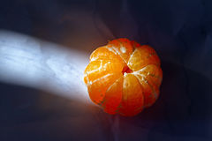 The peeled tangerine lighted sun rays Royalty Free Stock Image