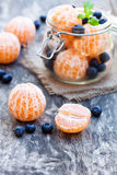 Peeled  tangerine or mandarin fruit and blueberry in glass jar o Stock Photo