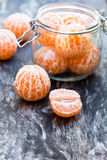 Peeled  tangerine or mandarin  fruit in glass jar on wooden table Royalty Free Stock Photography