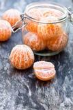 Peeled   tangerine or mandarin fruit in glass jar on wooden table Royalty Free Stock Image