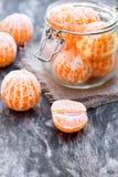 Peeled  tangerine  or mandarin fruit in glass jar on wooden table Stock Photos