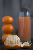Peeled tangerine mandarine. With glass of juice and few tangerines as blurred background Royalty Free Stock Images