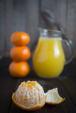 Peeled tangerine mandarine. With jug of fresh juice and few tangerines as blurred background Royalty Free Stock Image