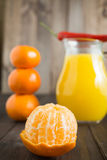 Peeled tangerine mandarine. With jug of fresh juice pepper chili on top and few tangerines as blurred background Royalty Free Stock Photo
